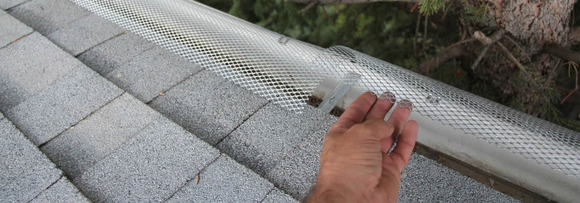 One hand lifts up the aluminum gutter guard which has been clipped to the gutter.