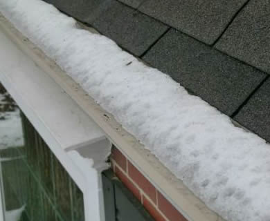 Micro mesh gutter guard with snow and ice on it.