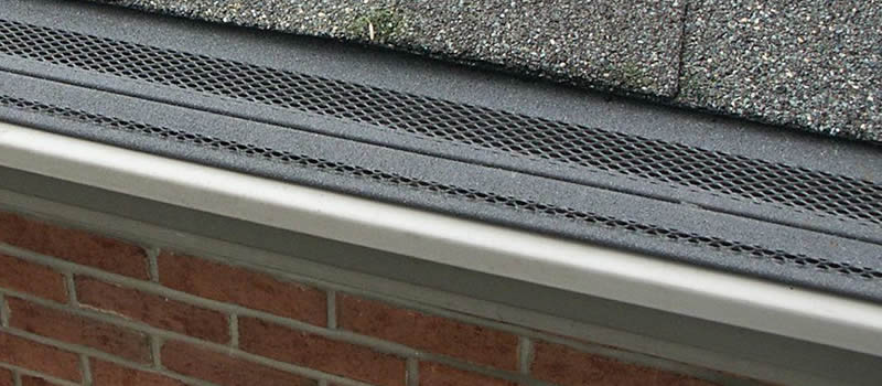 Steel shingle gutter guard installed on the roof.